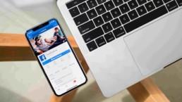 Laptop i telefon z wyświetlonym Facebookiem na szklanym stole