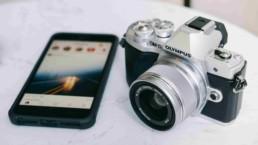 Telefon z włączonym ekranem i Instagramem oraz aparat marki Olympus na marmurowym stole
